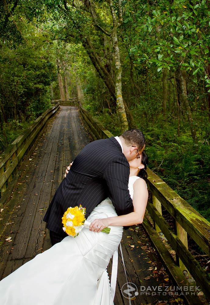 Newly weds kiss on a bridge through the woods.